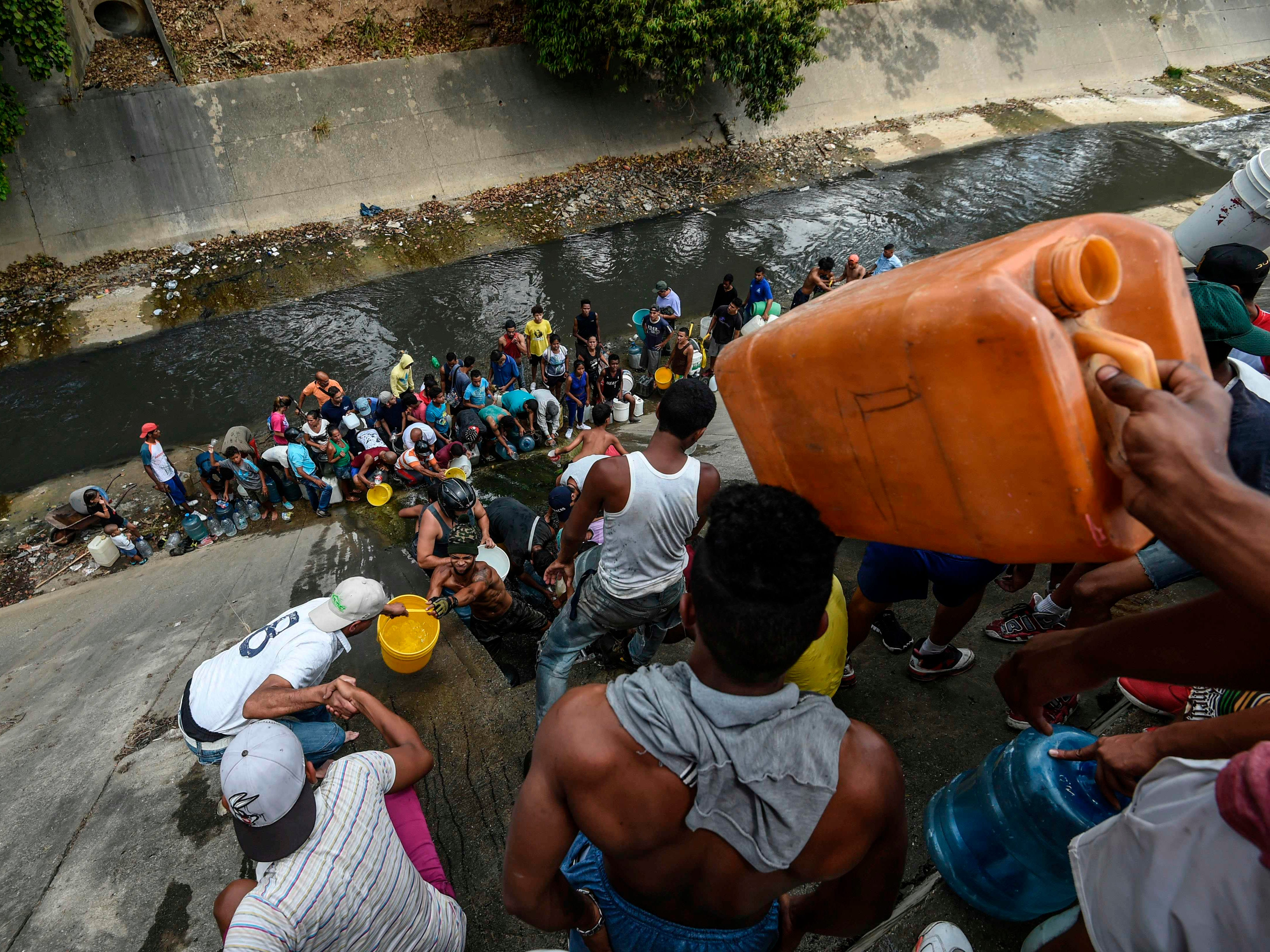 People from a leaking pipeline along the banks of the Guaire River in Caracas on March 11, 2019.