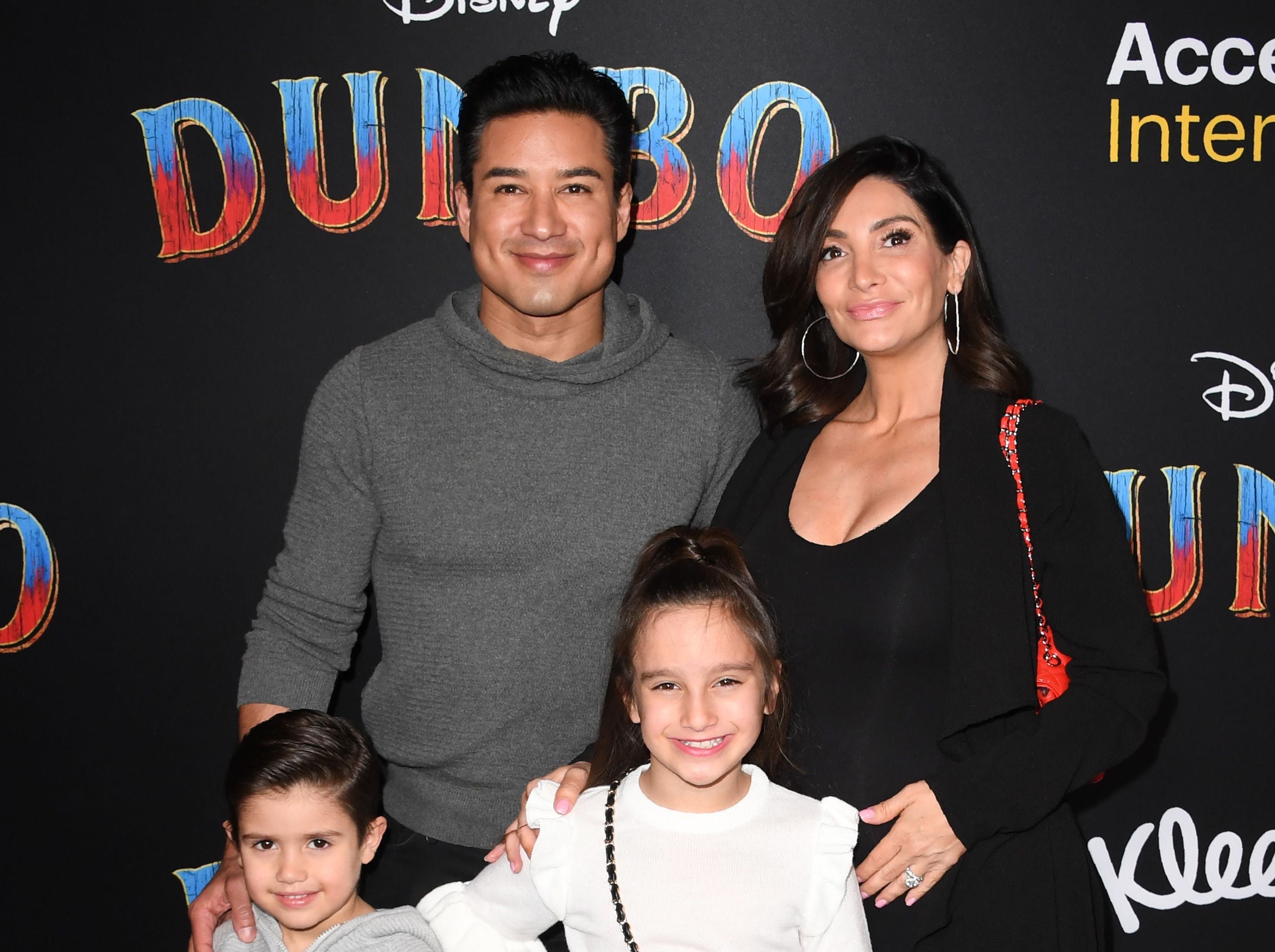 """TV host Mario Lopez, his wife Courtney Laine Mazza and kids Dominic Lopez (L) and  Gia Francesca Lopez (R) arrive for the world premiere of Disney's """"Dumbo"""" at El Capitan theatre on March 11, 2019 in Hollywood. (Photo by Robyn Beck / AFP)ROBYN BECK/AFP/Getty Images ORG XMIT: Premiere ORIG FILE ID: AFP_1EI2A6"""