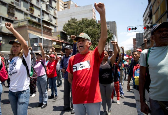 Members of the Bolivarian Militia stand in formation outside Miraflores presidential palace in Caracas, Venezuela, Tuesday, March 12, 2019. Members of the militia, which were formed the late President Hugo Chavez, met to show support for embattled President Nicolas Maduro after nearly a week of national blackouts while their country reels from economic and political calamity.