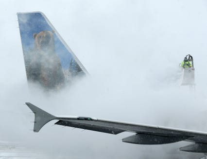 This file photo from January 2015 shows a worker de-icing a Frontier Airlines plane at LaGuardia Airport in New York.