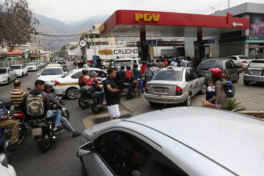 Venezuelans line up to refuel their vehicles at one of the few PDV gas stations with power on March 8, 2019 in Caracas.