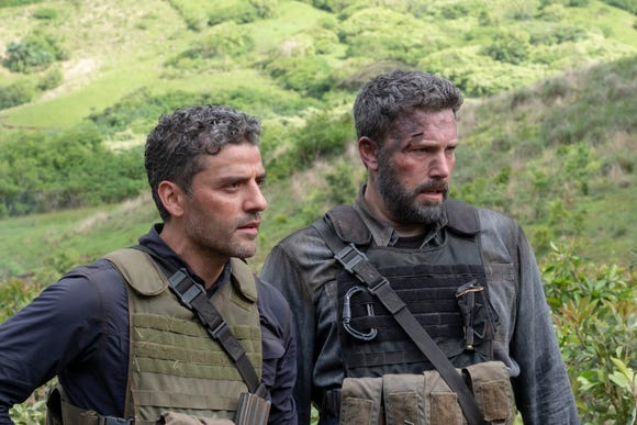 "Pope (Oscar Isaac, left) and Redfly (Ben Affleck) butt heads about how to get home with their stolen cash in ""Triple Frontier."""