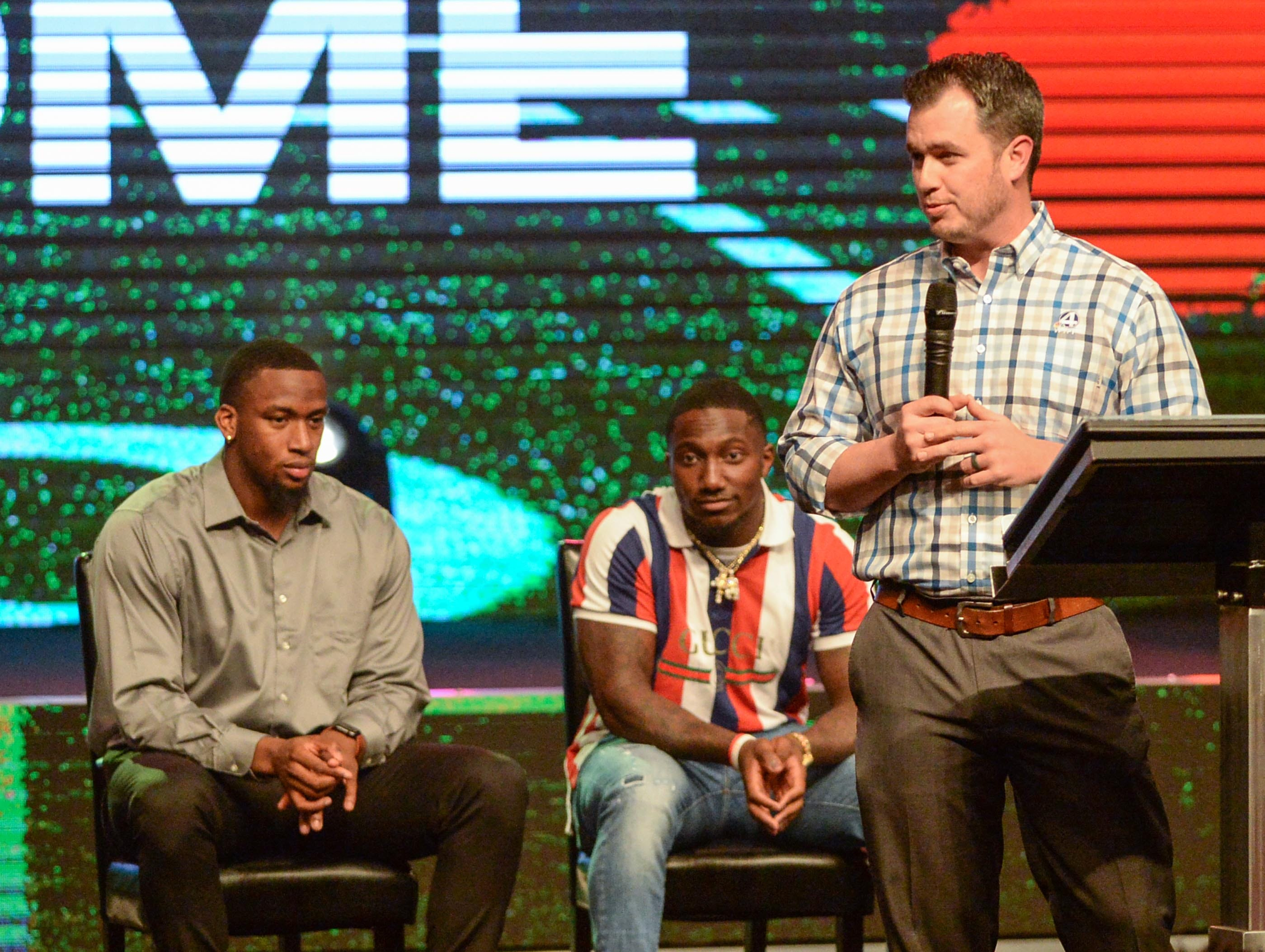 Brad Fralick, right, Sports Director for WYFF station introduces Clelin Ferrell and Deebo Samuel, former Clemson Tigers and South Carolina Gamecocks football players, during the Coaches 4 Character event at Relentless Church in Greenville Tuesday.