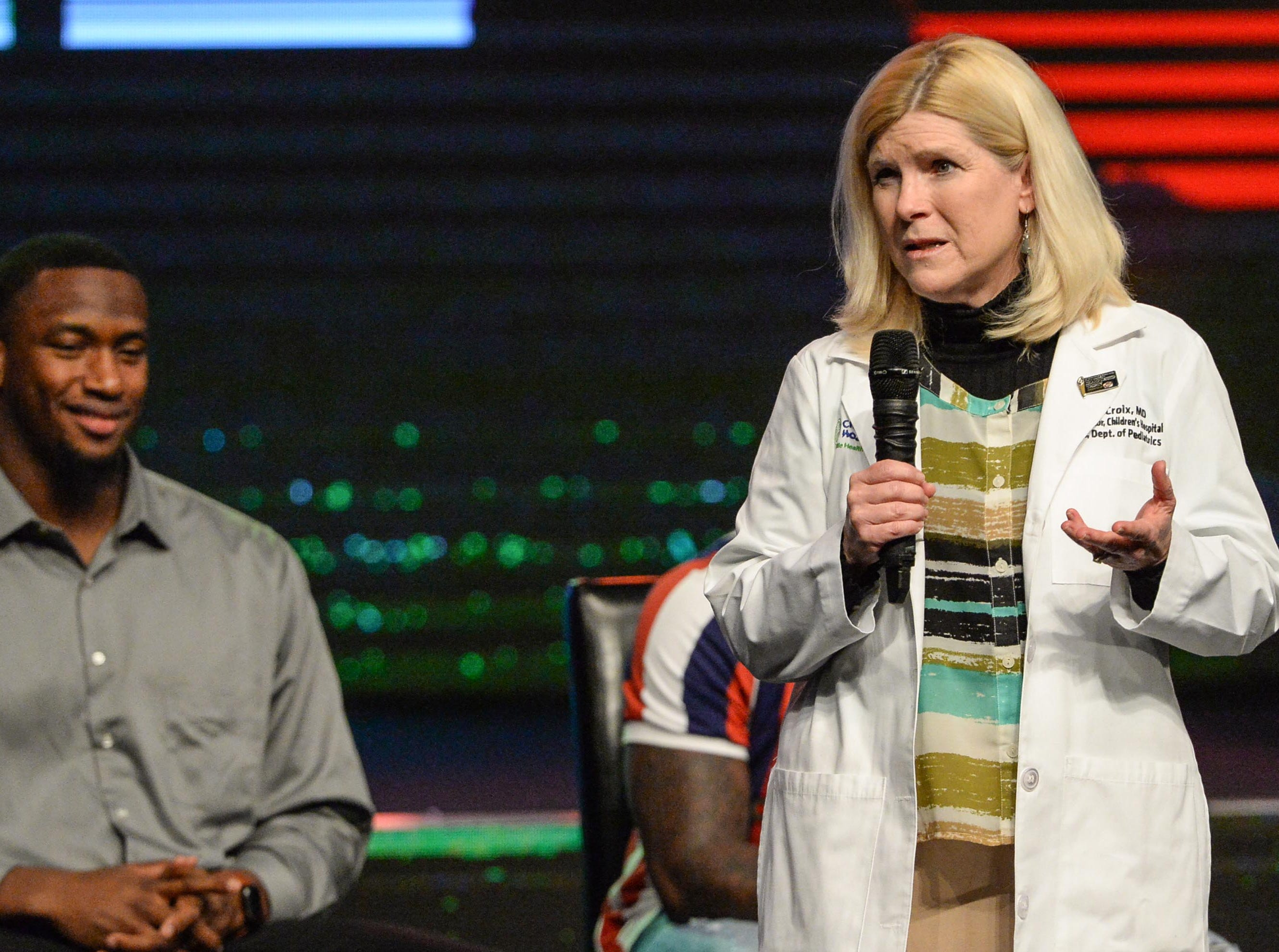 Dr. Robin LaCroix, medical director of Children's Hospital of PRISMA speaks near Clelin Ferrell and Deebo Samuel, former Clemson Tigers and South Carolina Gamecocks football players, during the Coaches 4 Character event at Relentless Church in Greenville Tuesday.