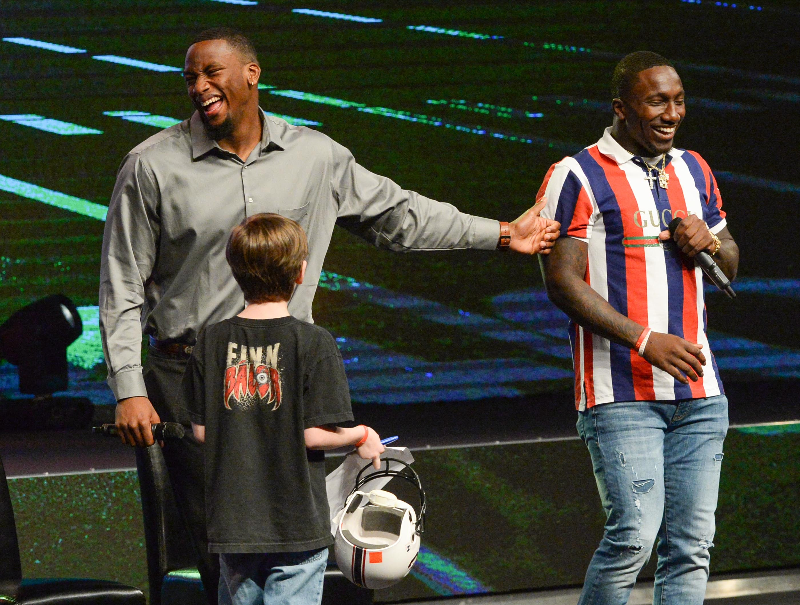 """Former Clemson Tiger Clelin Ferrell, left, and Deebo Samuel, right, South Carolina Gamecock football player, share a laugh after answering a question from Gene Johnson ask a question during the Coaches 4 Character event at Relentless Church in Greenville Tuesday. """"Put it in the bank,"""" both said."""