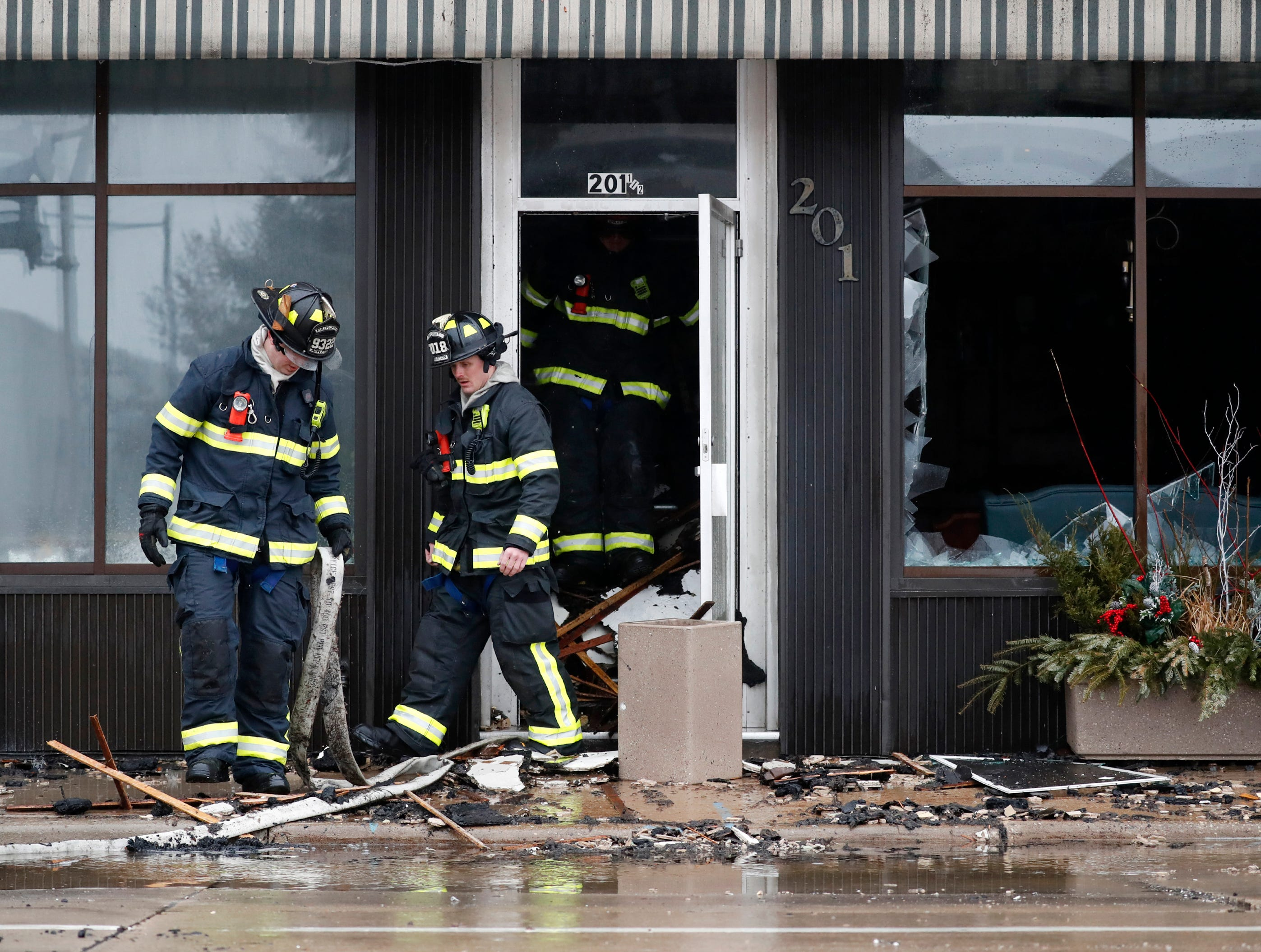Firefighters pull a hose out of the stairwell after working to put out a structure fire in downtown Appleton on the corner of West Washington and North Appleton Streets Wednesday, March 13, 2019, in Appleton, Wis. Danny Damiani/USA TODAY NETWORK-Wisconsin