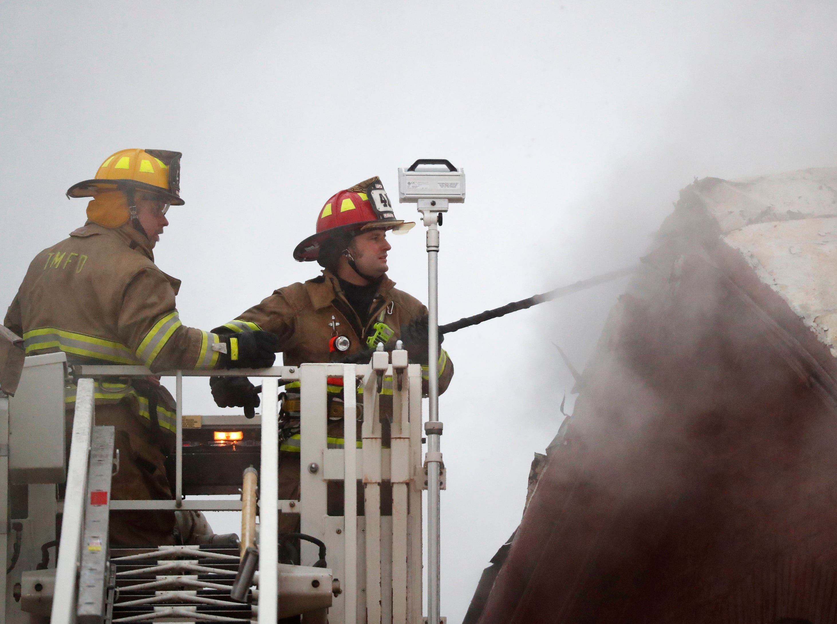 Firefighters open the peak of the roof while putting out a structure fire in downtown Appleton on the corner of West Washington and North Appleton Streets Wednesday, March 13, 2019, in Appleton, Wis. Danny Damiani/USA TODAY NETWORK-Wisconsin