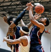 Fairleigh Dickinson's Mike Holloway Jr., left, and Darnell Edge, right, battle for a rebound with St. Francis Pa.'s Jamaal King