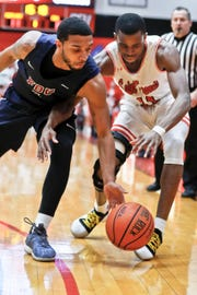 Fairleigh Dickinson's Darnell Edge (1) and St. Francis Pa.'s Isaiah Blackmon chase after a loose ball during the NEC Final.