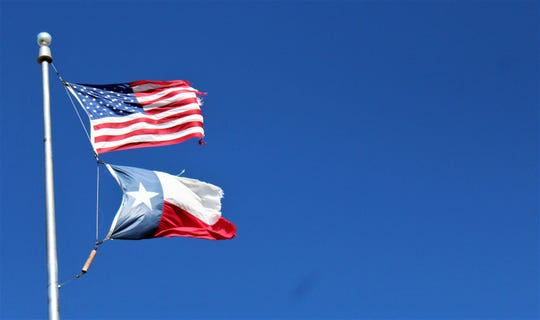 Flags at the Texas Department of Transportation offices in northwest Abilene are fully extended by high winds Wednesday. Nearby, TxDOT's 300-foot tower was toppled by wind.