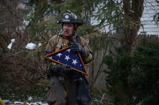 Firefighter Jim Mervyn carries a military burial flag recovered from the house on 32nd Street.