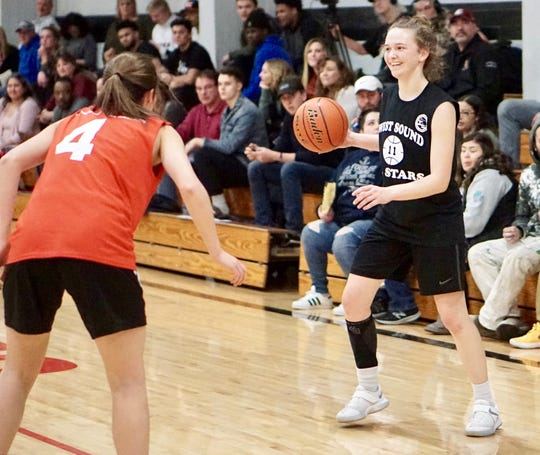 North Kitsap's Raelee Moore smiles as she looks to make a pass during Tuesday's West Sound Senior High School All-Star girls basketball game at Olympic College.