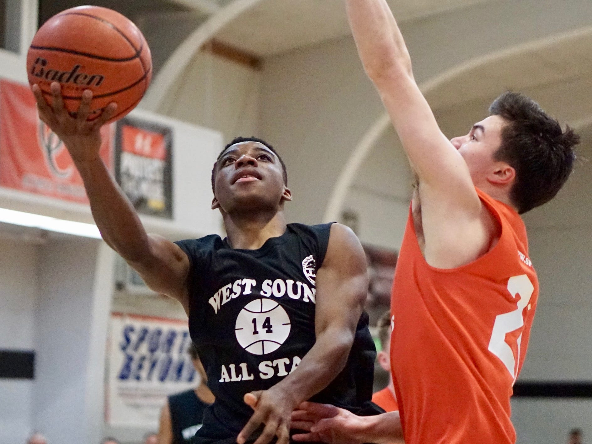 Central Kitsap's Elijah McGee goes to the basket while Olympic's Brandon Barron defends during Tuesday's West Sound Senior High School All-Star boys basketball game at Olympic College.