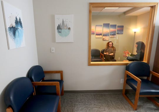 Josephine Price, left, and Beth Friedman-Darner are framed in the two-way mirror of an observation room as they talk about Kitsap Mental Health Child and Family Services on Tuesday. The two work with a program that assists families whose children face mental health challenges, and it has a new home off Highway 303.