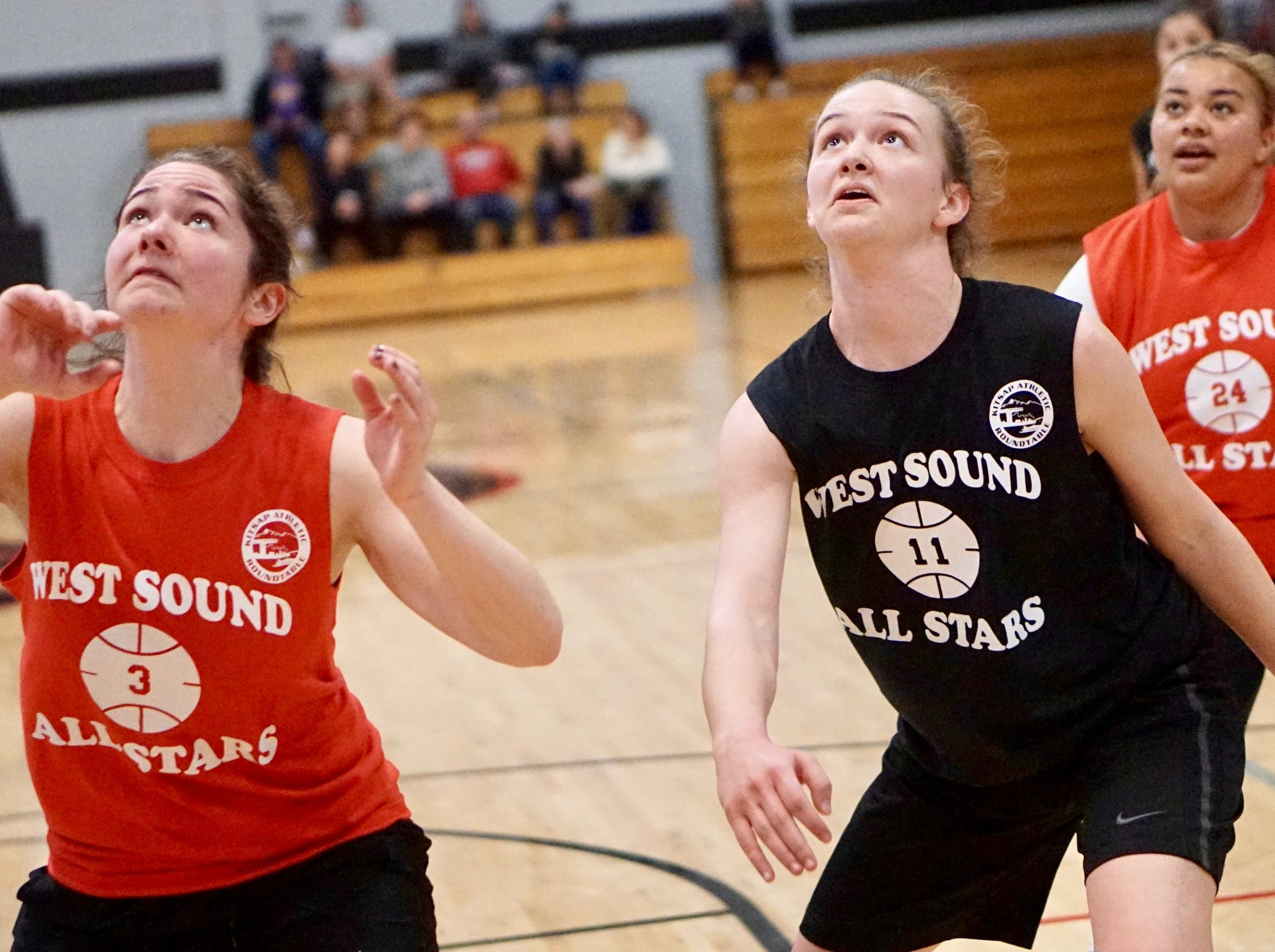 Olympic's Zoie Matheny (left) and North Kitsap's Raelee Moore eye a rebound during Tuesday's West Sound Senior High School All-Star Basketball Games at Olympic College.