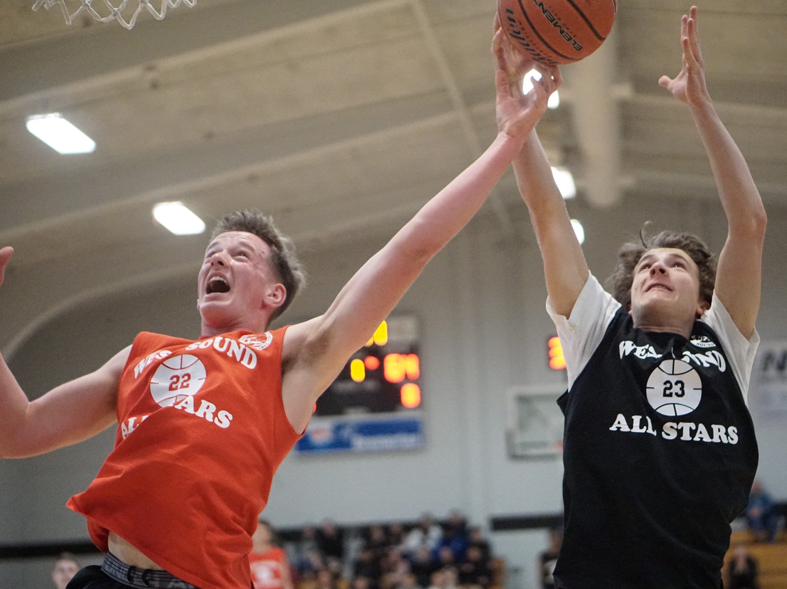 Crosspoint's Alex Weirth (left) and North Kitsap's Grant Baker fight for a rebound during Tuesday's West Sound Senior High School All-Star Basketball Games at Olympic College.