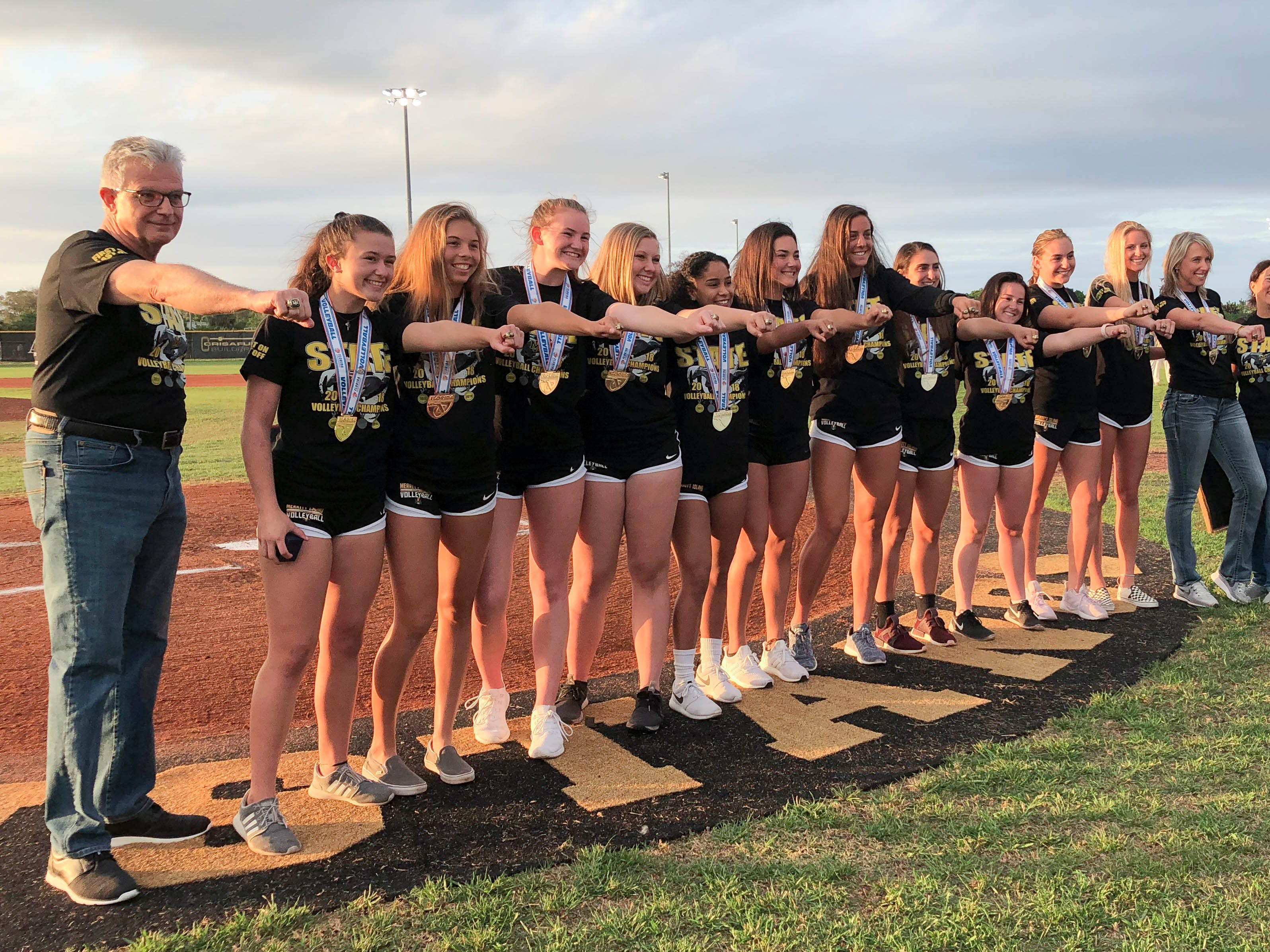 Merritt Island volleyball players, coaches and. Trainers show off their State Championship rings they received before Tuesday's baseball game against Eau Gallie.