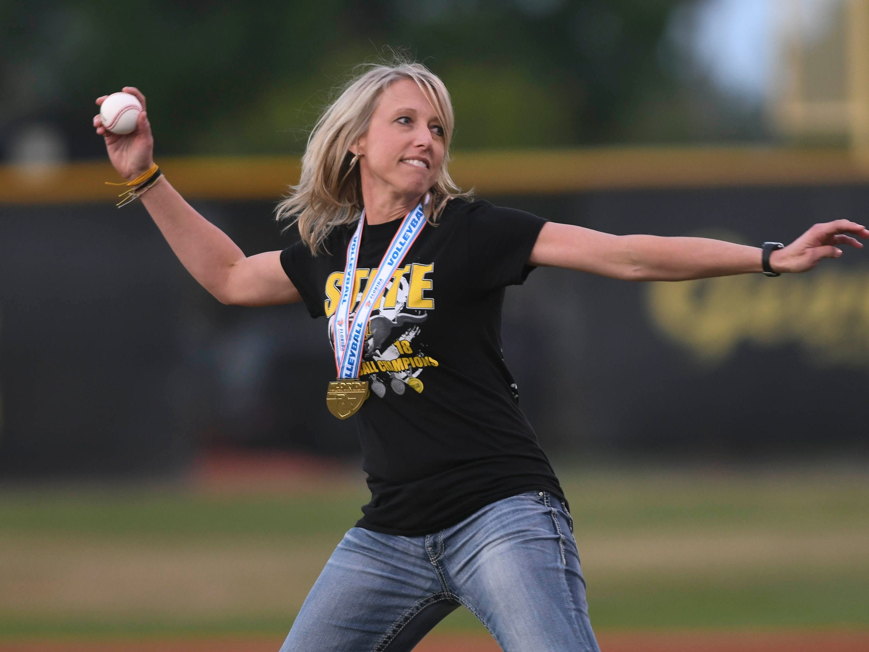 Merritt Island volleyball head coach Angie Patrick throws out the first pitch before Tuesday's baseball game against Eau Gallie. The Mustang volleyball team was presented with their State Championship rings prior to the game.