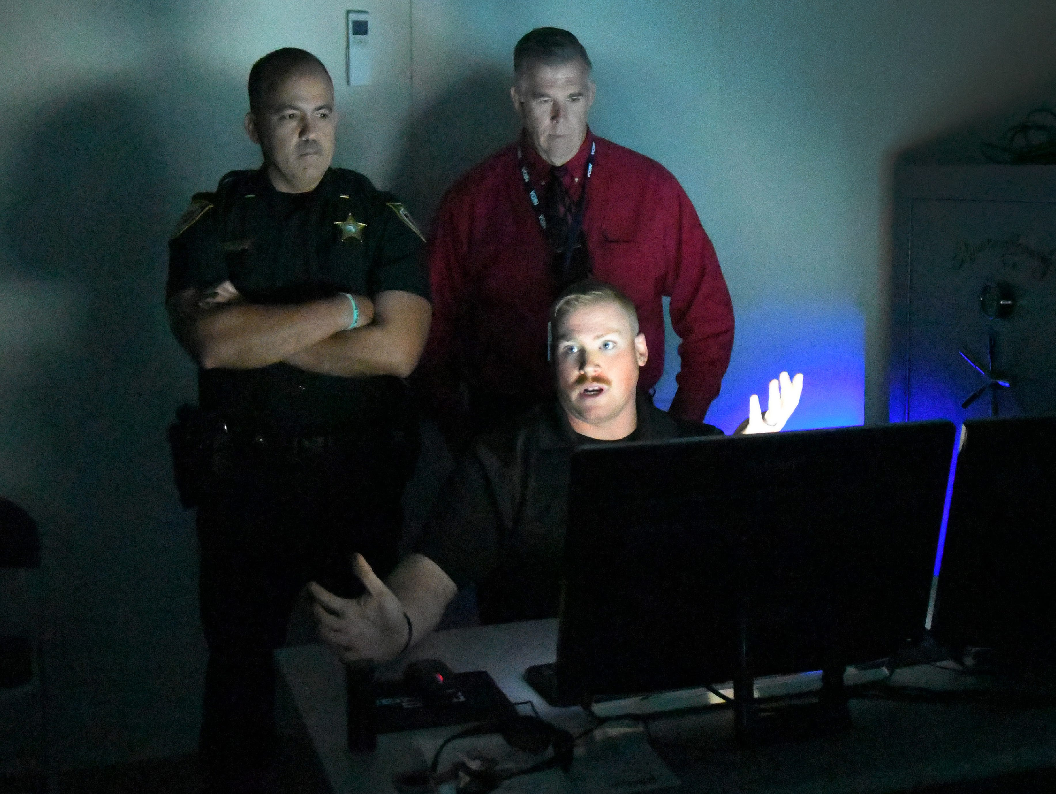 Corporal Jeremy Flake, at the controls, describes the workings of the the MILO Range 300 Theater, a high tech interactive training system, set up at a Brevard County Sheriff's Office facility in Sharpes. It is part of a program to help  train school guardians. Those using the MILO Range are armed with simulated handguns, and immersed in a 300 degree video simulating an active shooting situation in a school, office, and other locations.