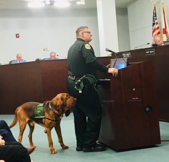 Brevard County Sheriff Wayne Ivey, accompanied by bloodhound Junny, addresses Brevard County commissioners in support of a proposed  ordinance that would restrict the sales of dogs and cats in pet stores.
