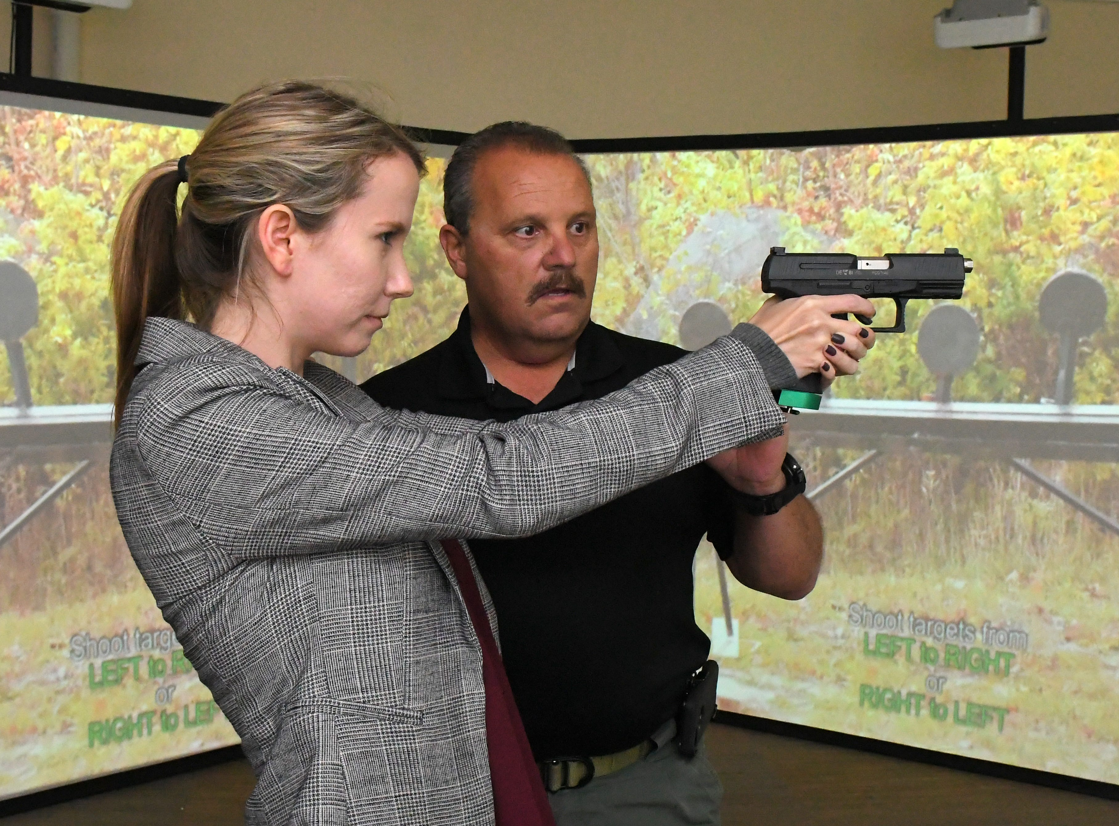 FLORIDA TODAY education reporter Caroline Glenn tries out the MILO Range 300 Theater with assistasnce from Cpl. Larry Plotkin. The MILO Range 300 Theater, a high tech interactive training system, is set up at a Brevard County Sheriff's Office facility in Sharpes. It is part of a program to help  train school guardians. Those using the MILO Range are armed with simulated handguns, and immersed in a 300 degree video simulating an active shooting situation in a school, office, and other locations.
