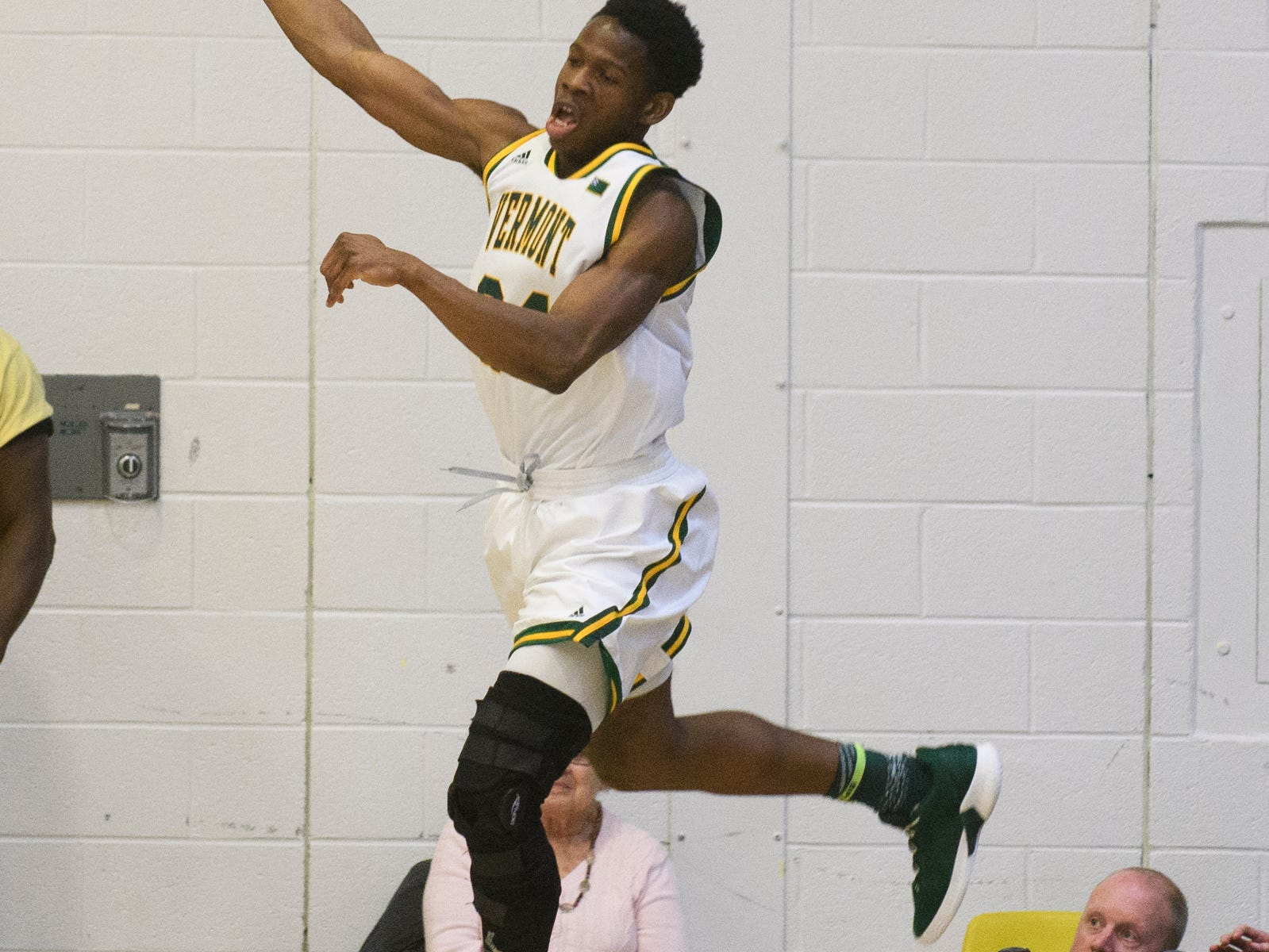 Vermont guard Ben Shungu (24) leaps to save the ball from going out of bounds during the America East semifinal game between the Binghamton Bearcats and the Vermont Catamounts at Patrick Gym on Tuesday March 12, 2019 in Burlington, Vermont.