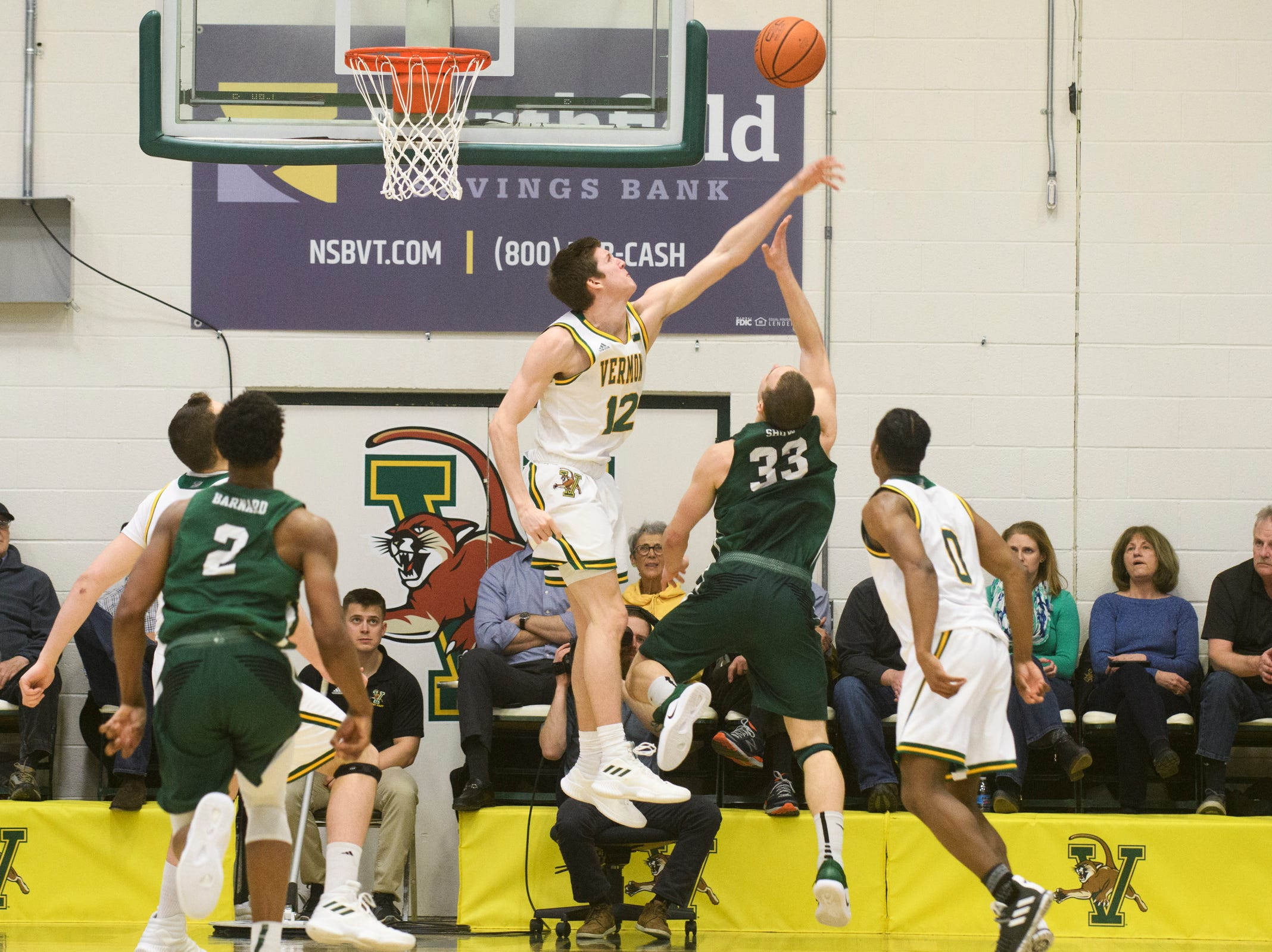 Vermont forward Bailey Patella (12) blocks the shot by Binghamton's J.C. Show (33) during the America East semifinal game between the Binghamton Bearcats and the Vermont Catamounts at Patrick Gym on Tuesday March 12, 2019 in Burlington, Vermont.