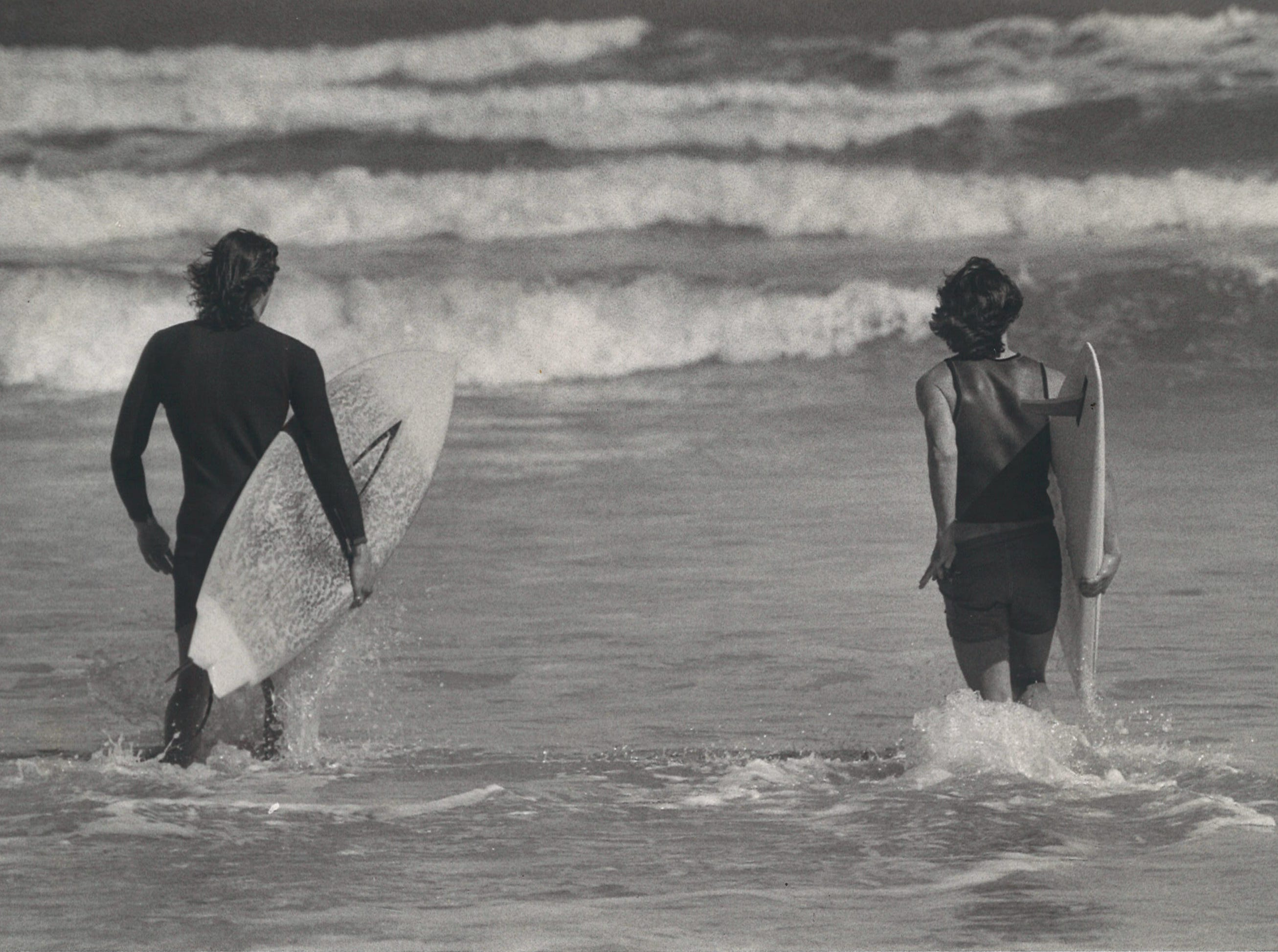 Surfers head out into the waves on Mustang Island in Corpus Christi in April 1977.