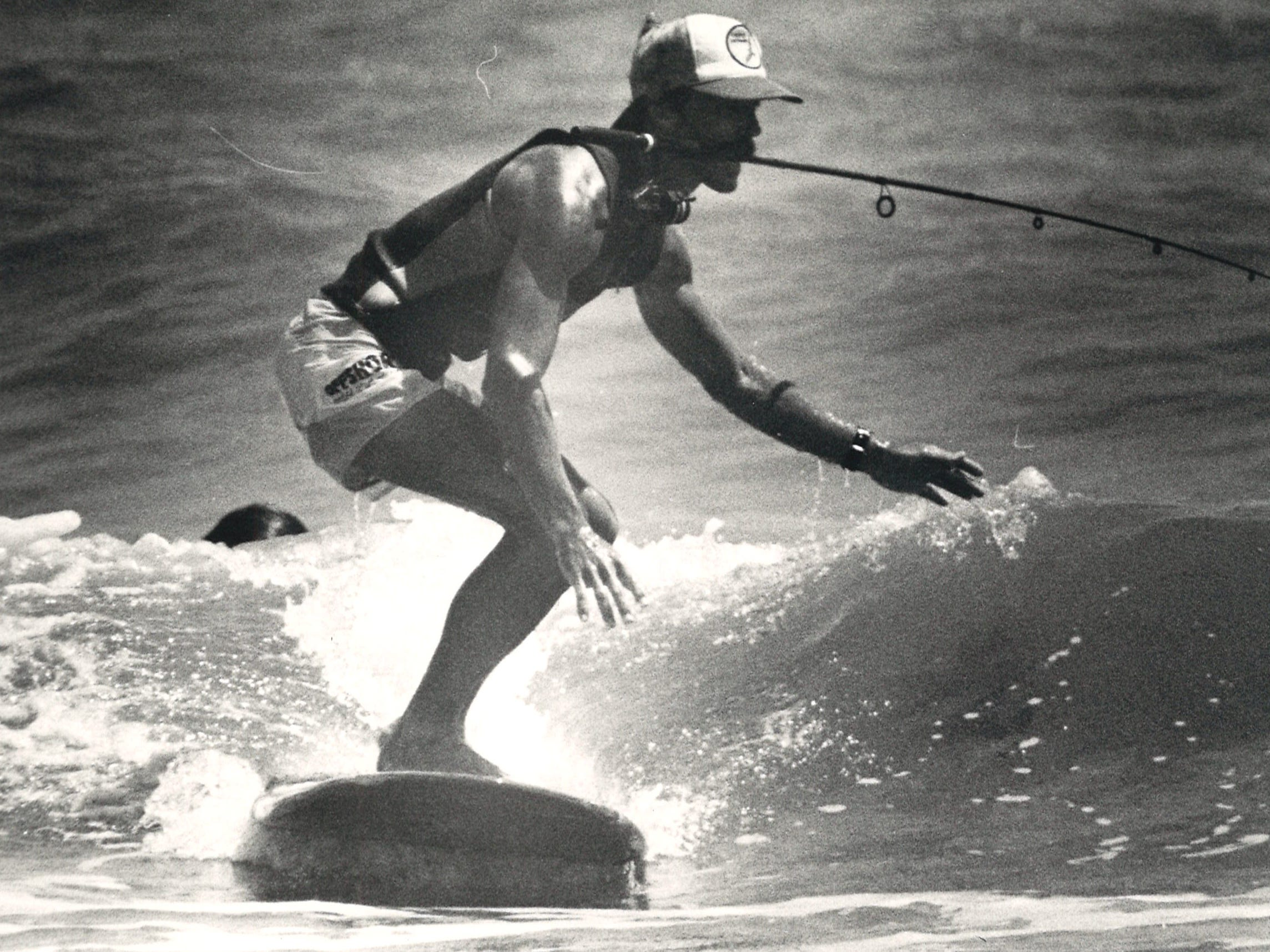 A surfer clutches a fishing rod in his mouth during the Off Shore/Raisins Texas Pro Am Surfing Classic at J.P. Luby Surf Park in Corpus Chrisit on March 29, 1986.