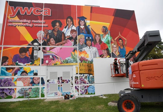 Sandra Gonzales and Monica Marie Garcia install mural panels at the YWCA, Tuesday, March 12, 2019. The mural unveiling is May 28.