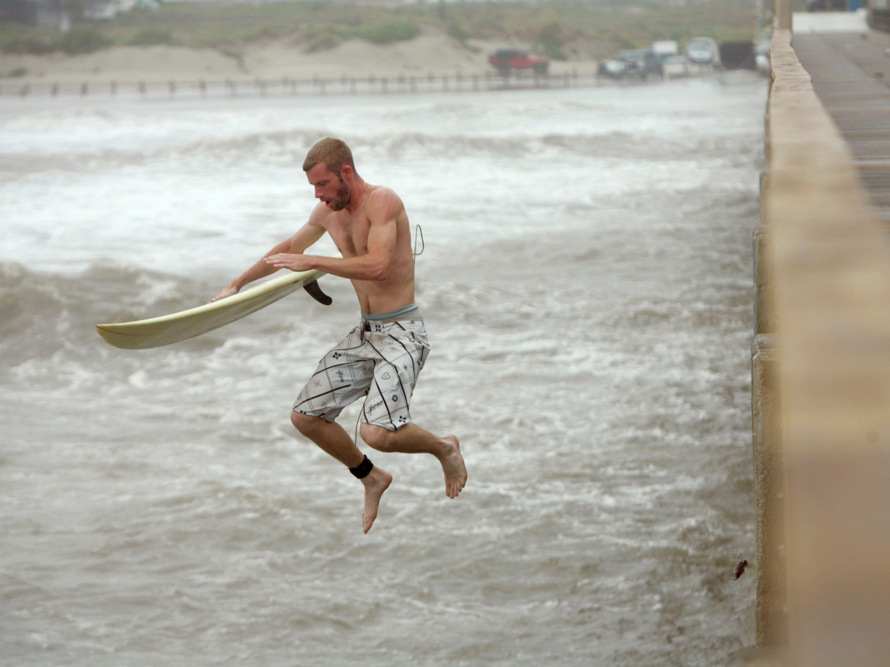 Chris Wilson of Alexandria, La., leaps off the pier Wednesday, June 30, 2010 as surfers take advantage of the big waves from Hurricane Alex at Horace Caldwell Pier in Port Aransas. Wilson said he drove down from Louisiana Tuesday just to come out and surf in the waves produced by the first hurricane of the season.