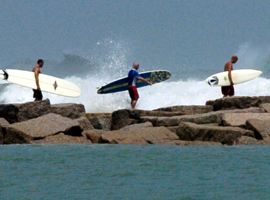 A group of surfers walks along the north side of the Port Aransas jetty Monday to catch some of the big waves churned up by Hurricane Katrina in the Gulf of Mexico in August 2005.