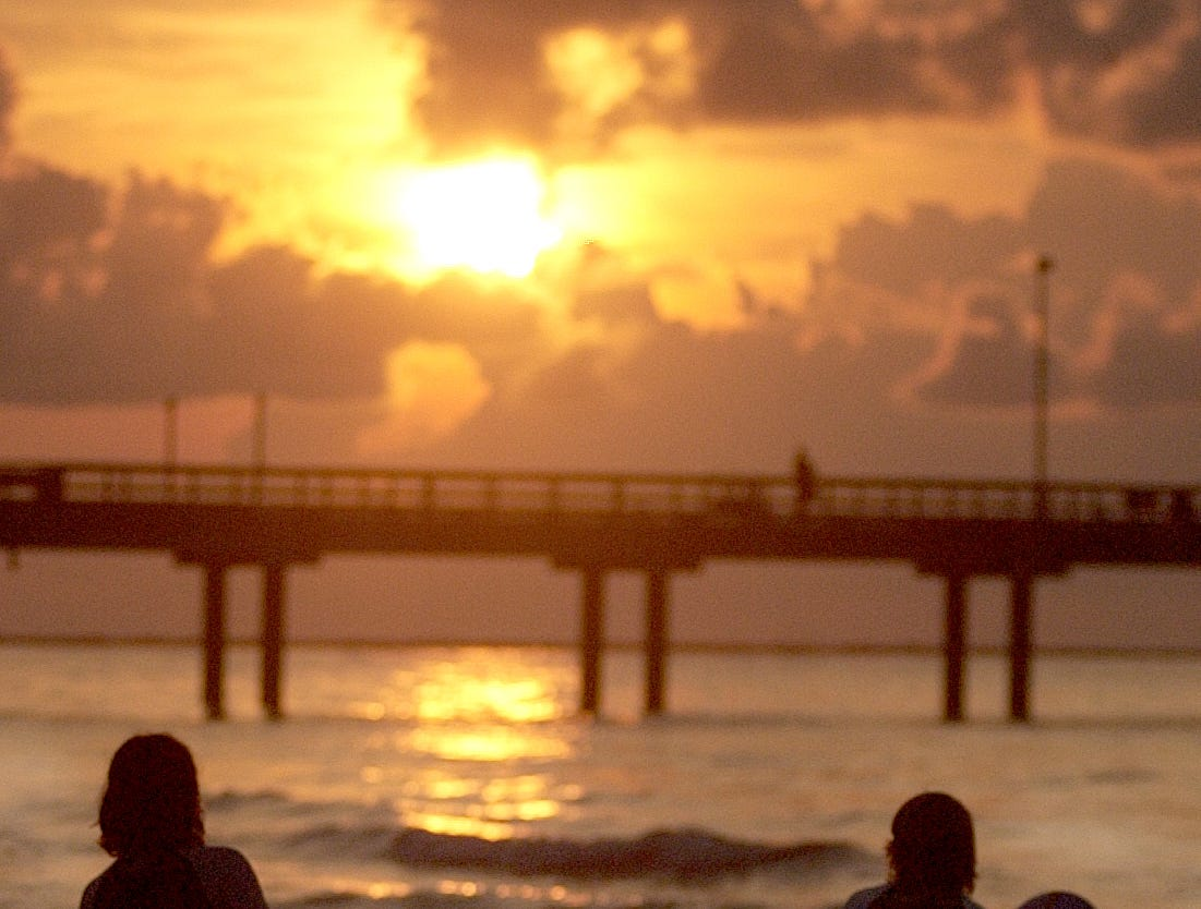 John McDonald, 16, and Ben Waid, 16, (left to right) both from New Braunfels, walk along the beach near Horace Caldwell Pier in Port Aransas, as they look for a place to surf Sunday morning, July 23, 2006 as the sun come up over the horizon.