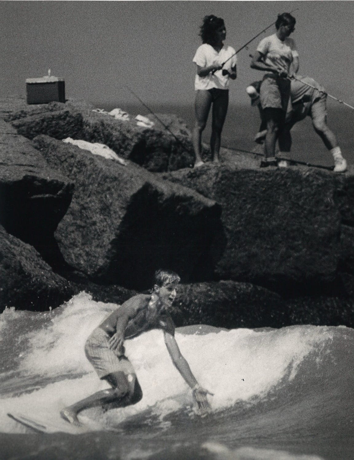 An unidentified surfer catches a wave next to the Fish Pash jetties in Mustang Island State Park in Corpus Christi in July 1987 as fishermen try their luck in the background.