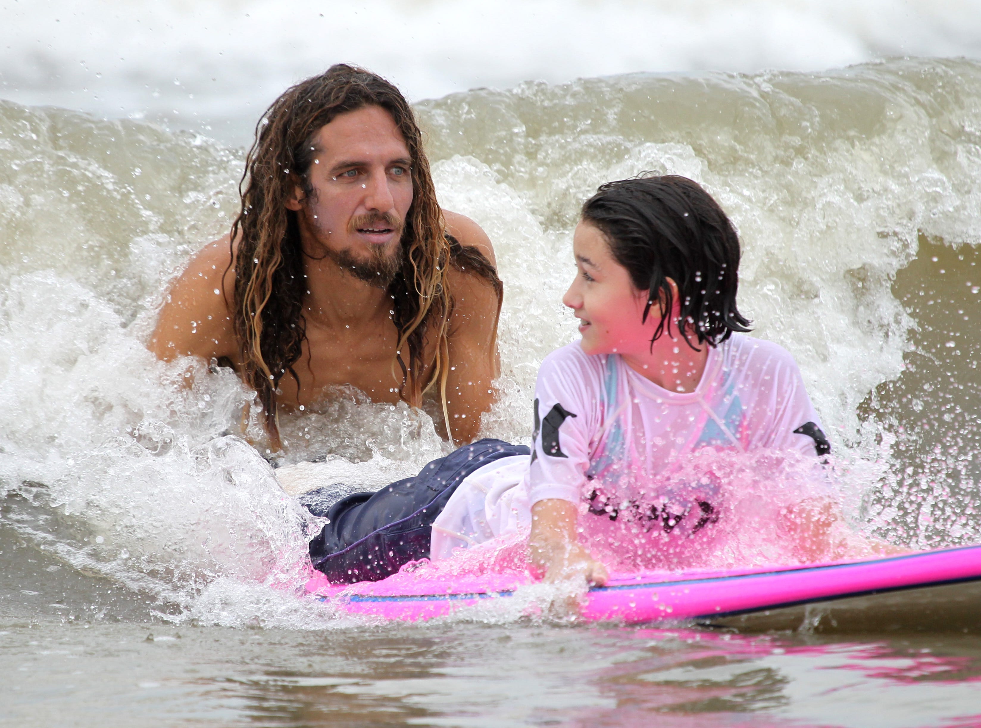 Professional surfer Rob Machado works with Phoebe Rivera, 12, as she participates in the Rip My Shred Stick surf competition at Bob Hall Pier on June 8, 2012. The free competition, which is in its second year, was open to youth 16 and younger.
