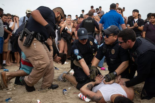 Police take two men in to custody on the beach after breaking up a fight during spring break 2019 in Port Aransas on Tuesday, March, 12, 2019.