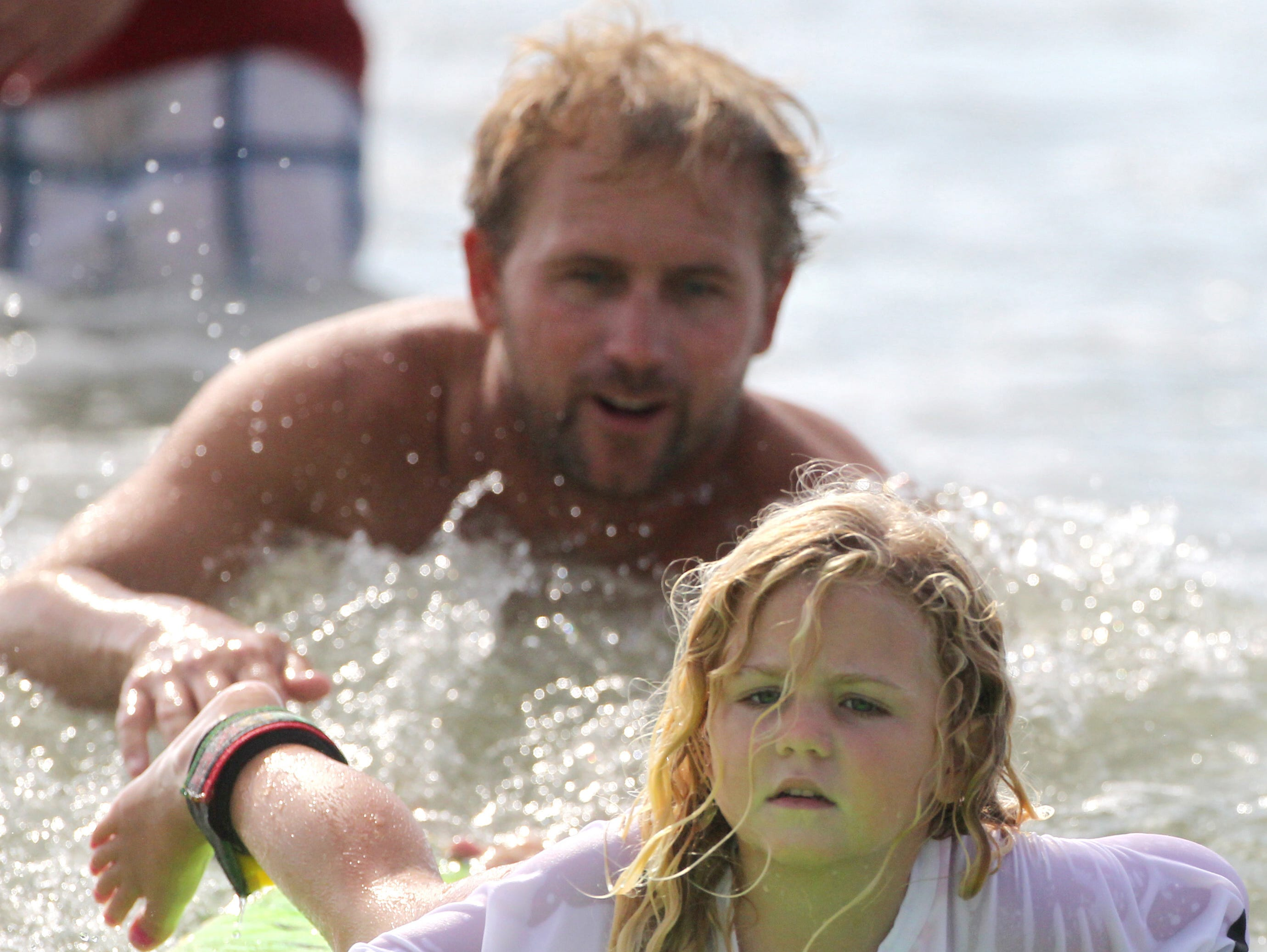 "Professional surfer Pat O'Connell works with new surfer Maris Browning, 4, as she gets on a board for the first time while participating in the 2011 Hurley ""Rip My Shred Stick"" surf competition at Bob Hall Pier on June 15, 2011."