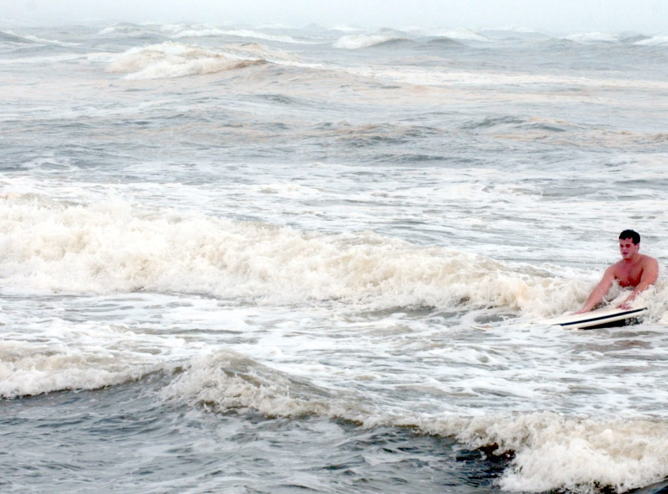 Will Shields of Houston makes his way back to shore through the rough surf near the Packery Channel north jetty in Corpuys Christi after surfing Monday, October 16, 2006.