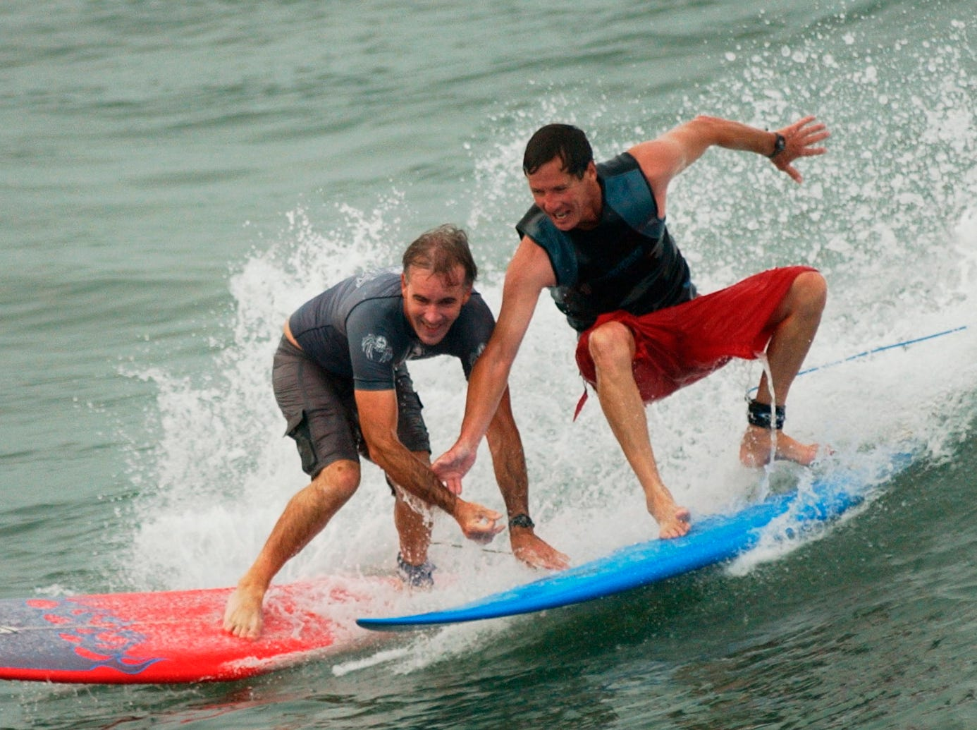 (l-r) Alan Lassiter (left) and Keith Adamson (right), both of Corpus Christi, clown around on a wave  while surfing at Horace Caldwell Pier on Port Aransas Friday, Aug. 15, 2003. Dozens of surfers took advantage of the storm inspired surf throughout the day Friday.