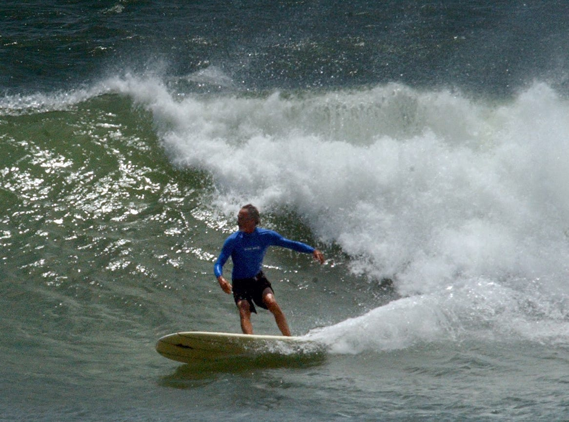 A surfer catches a wave breaking beyond the end of Horace Caldwell pier in Port Aransas Tuesday June 29, 2010. The waves generated by Tropical Storm Alex grew throughout the day.