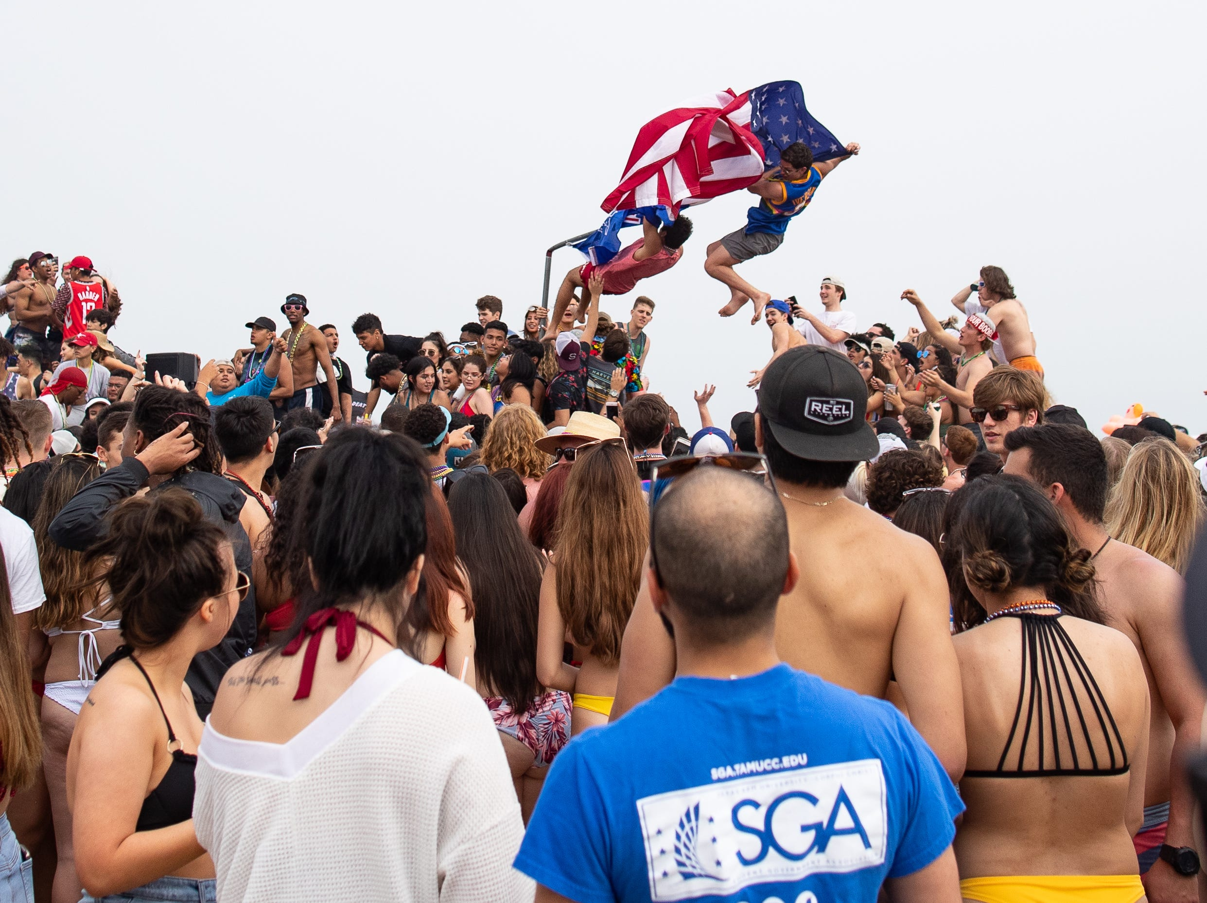 Two spring breakers fall as a flagpole in the bed of a pickup truck snaps in half during spring break 2019 in Port Aransas on Tuesday, March, 12, 2019.