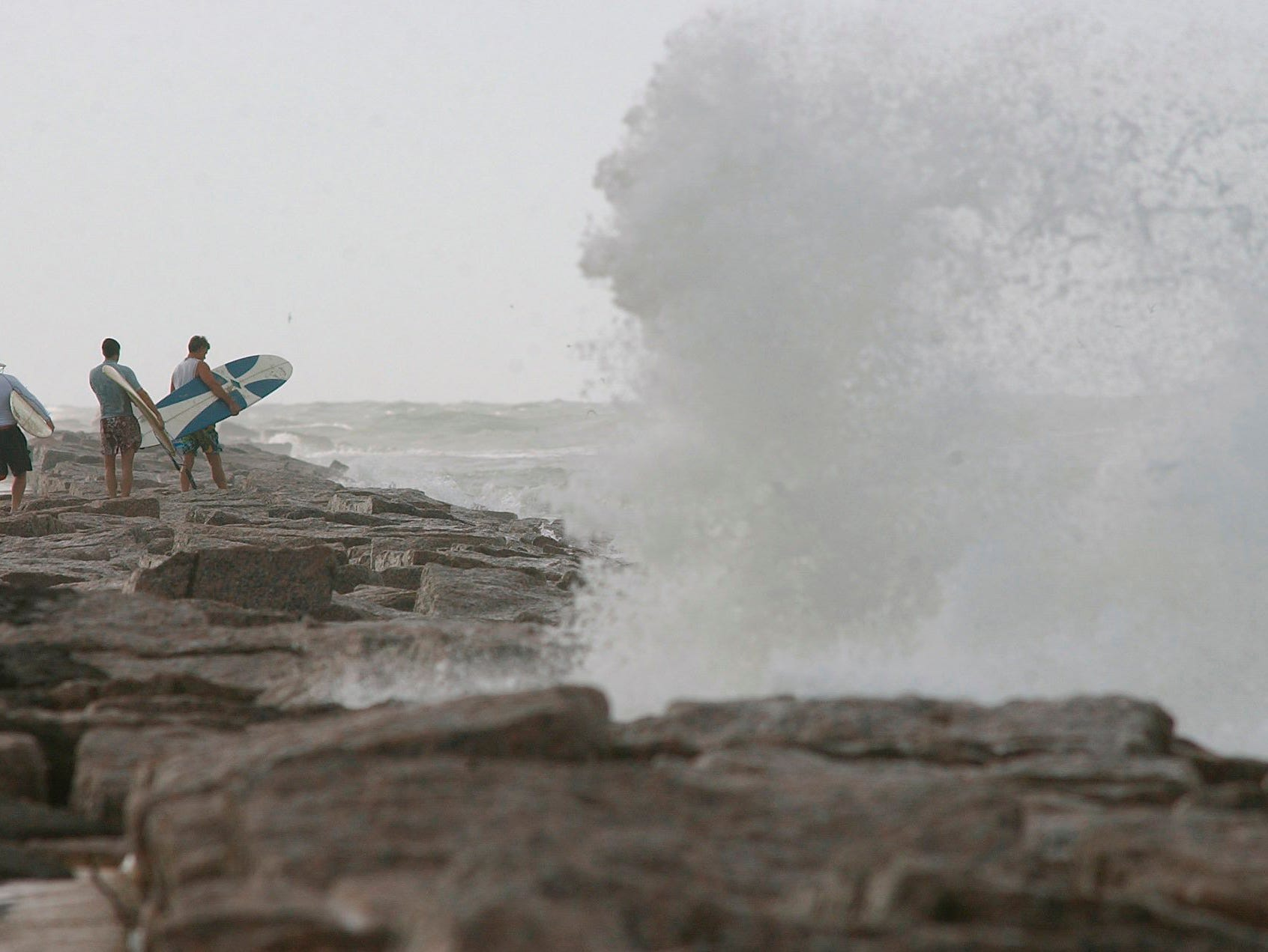 A wave crashes on the rocks at the south jetty in Port Aransas as three surfers look for a spot to jump into the surf brought in by Hurricane Erika on Aug. 16, 2003. (8-16-03 mcp)