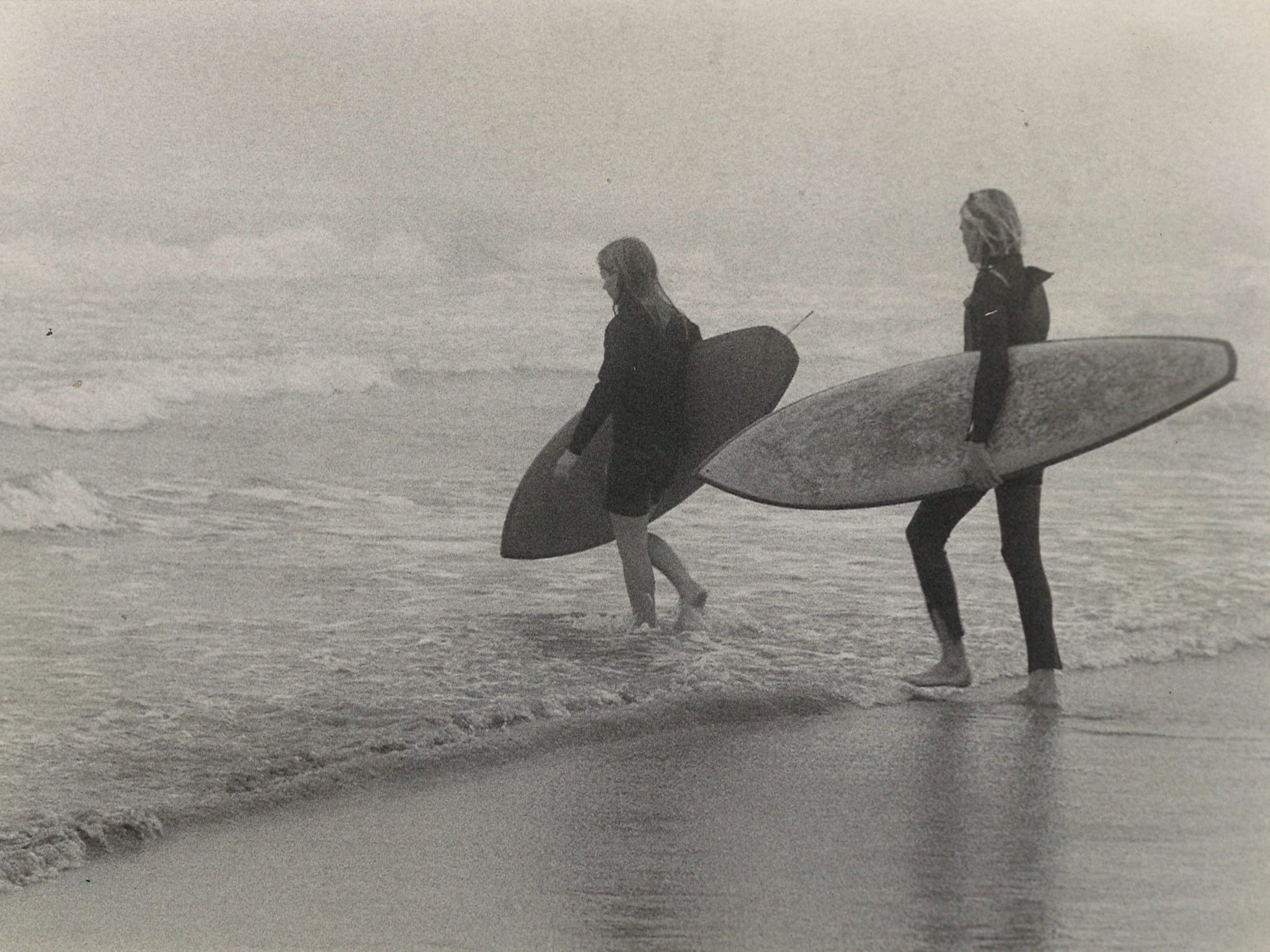Craig Adams (left) and John Watson, both 17, venture into the surf near Cole Park on Jan. 7, 1974. The fog and drizzle kept most people away.