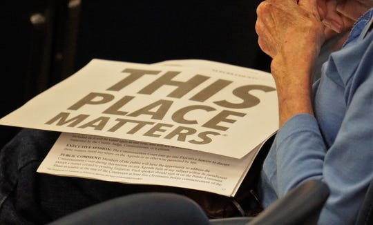 Signs in support of restoring the 1914 Nueces County Courthouse is held by an attendee at commissioners court on March 13, 2019.