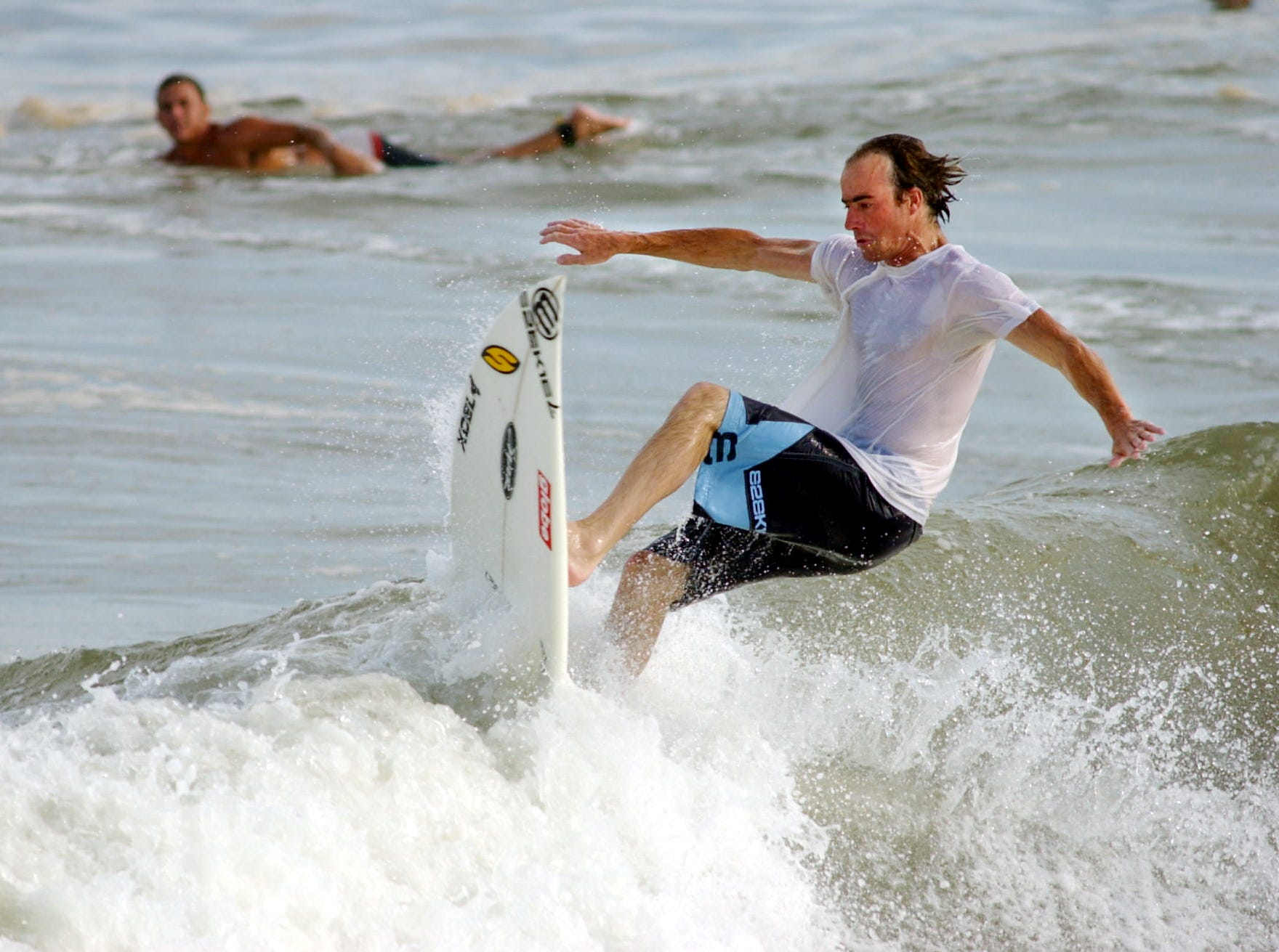 LOCAL -- Greg Pobst from California, surfs in the huge waves off Bob Hall Pier on Padre Island in Corpus Christi in September 2002. Tropical Storm Isidore churned up the waves, to the surfers' delight.