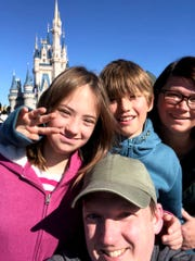 The Brooks family gather before Cinderella's Castle in the Magic Kingdom at Walt Disney World. Clockwise from left are Zoe and Finn Sullivan, mom Kim Brooks and dad Sean Sullivan.