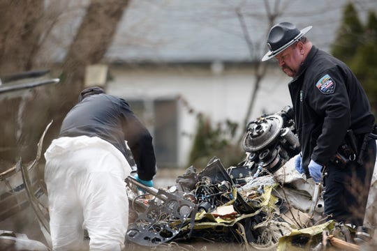Investigators work the scene of a plane crash on Wednesday, March 13, 2109, on Rollymeade Avenue in Madeira. The the pilot of the plane died due to the crash, which struck the back side of the house.