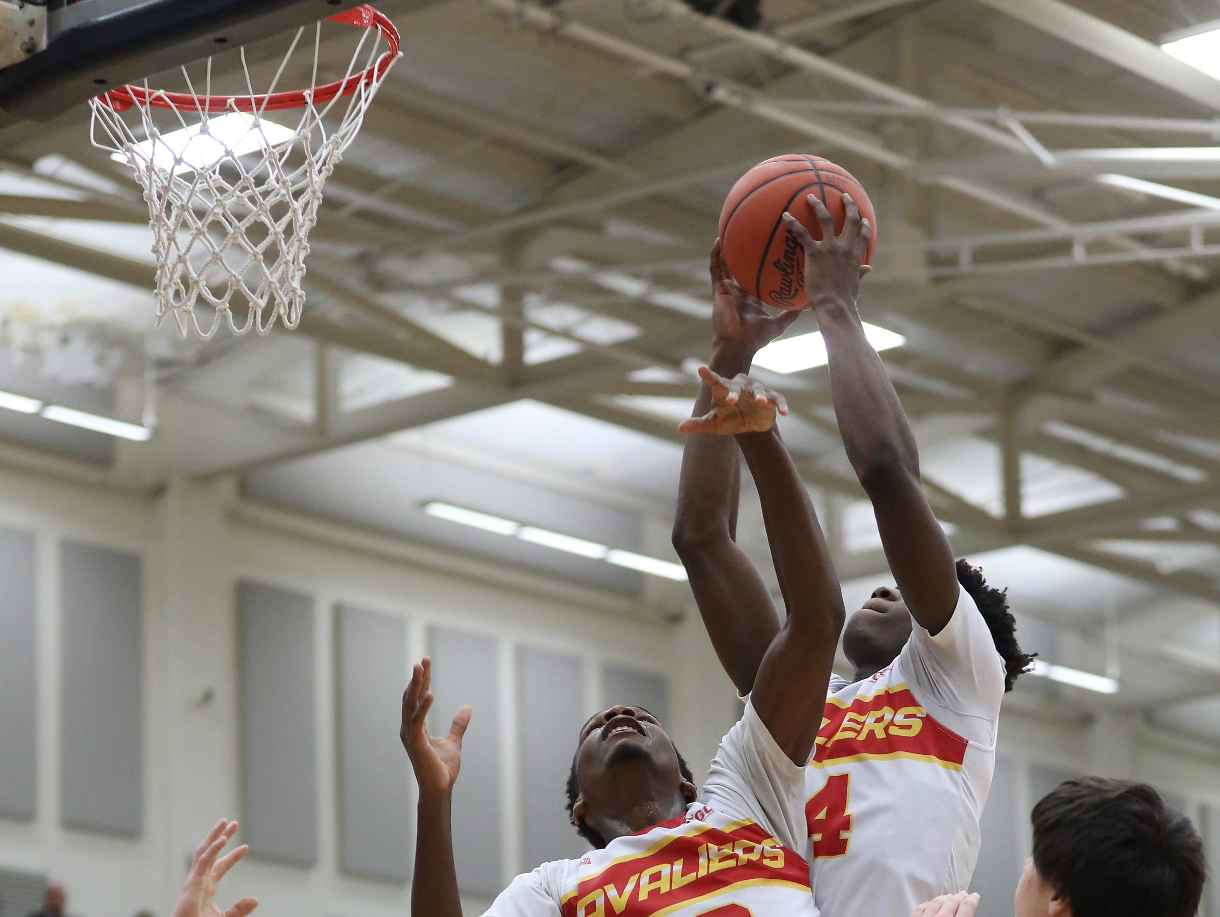 Purcell Marian players Bryan Warah and Alex Dotson  battle for a rebound during the Cavaliers' regional semi-final win against Versailles Wednesday, March 13, 2019.