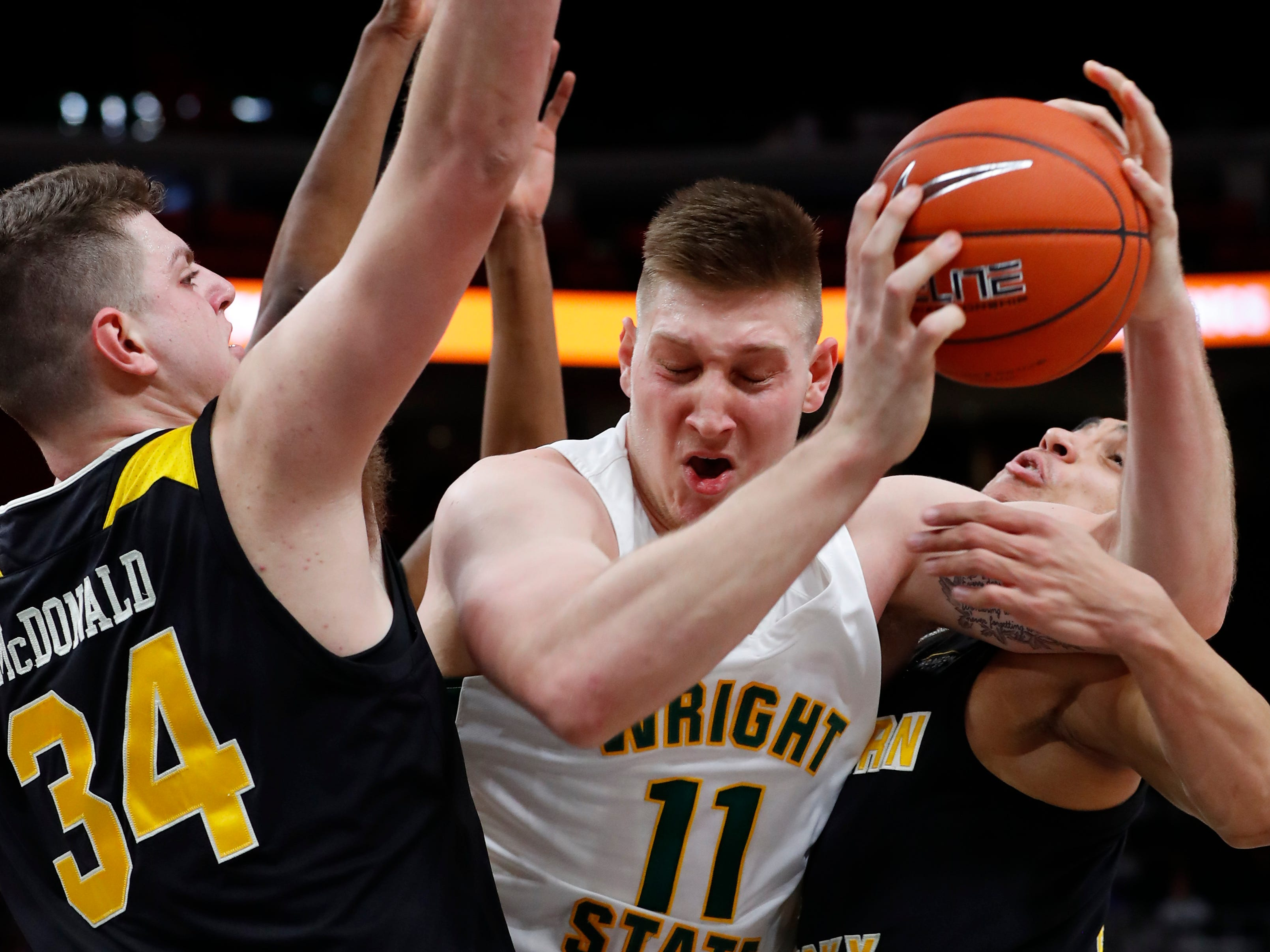Wright State center Loudon Love (11) tries to drive between Northern Kentucky forward Drew McDonald (34) and Northern Kentucky guard Paul Djoko (2) in the first half of an NCAA college men's basketball game in the Horizon League conference tournament championship in Detroit, Tuesday, March 12, 2019.