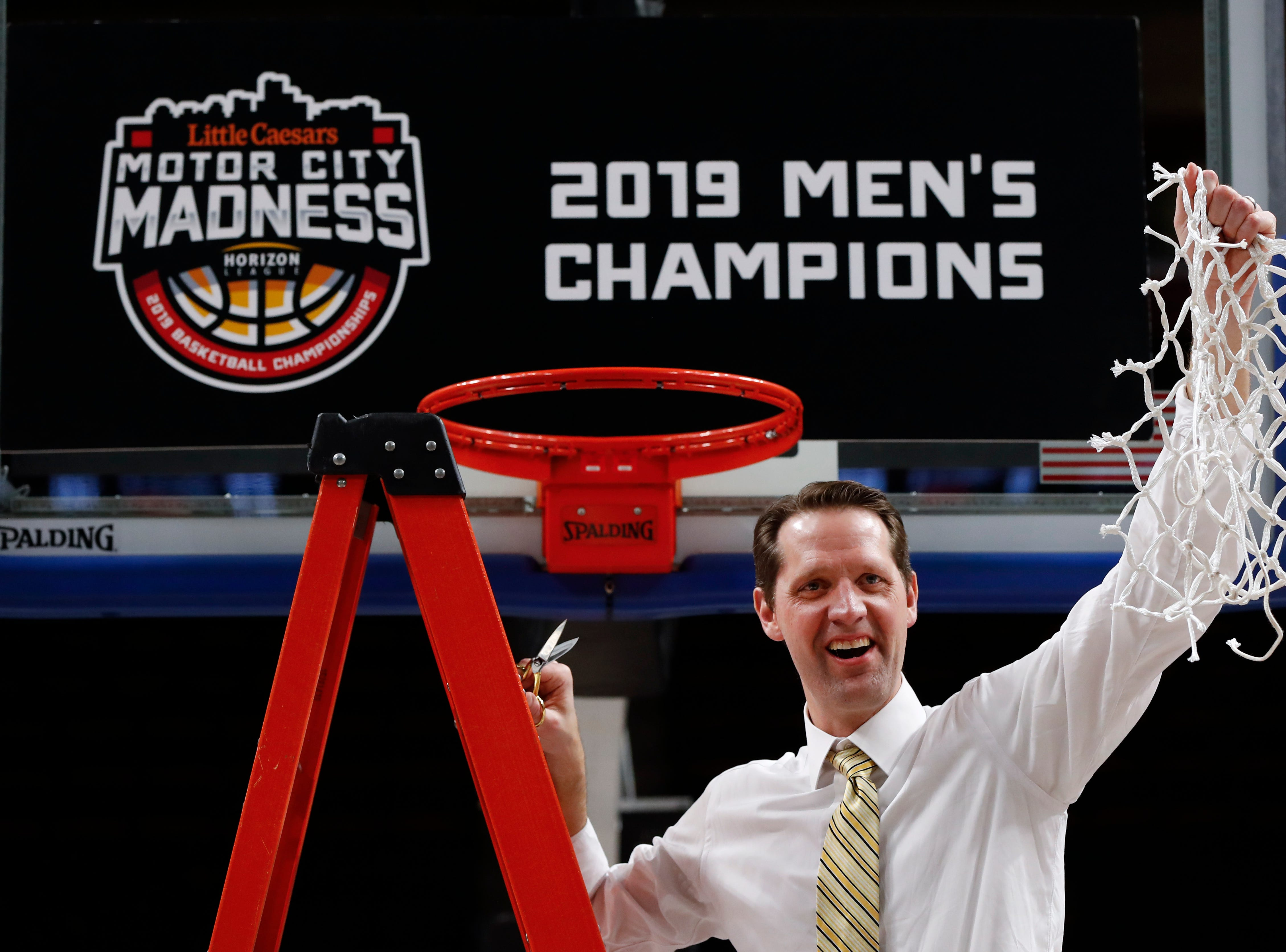 Northern Kentucky coach John Brannen holds up the net after the team's77-66 win against Wright State in an NCAA college basketball game for the Horizon League men's tournament championship in Detroit, Tuesday, March 12, 2019.